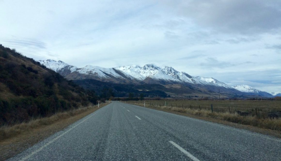 driving down road with mountains, snowcapped, grey skies
