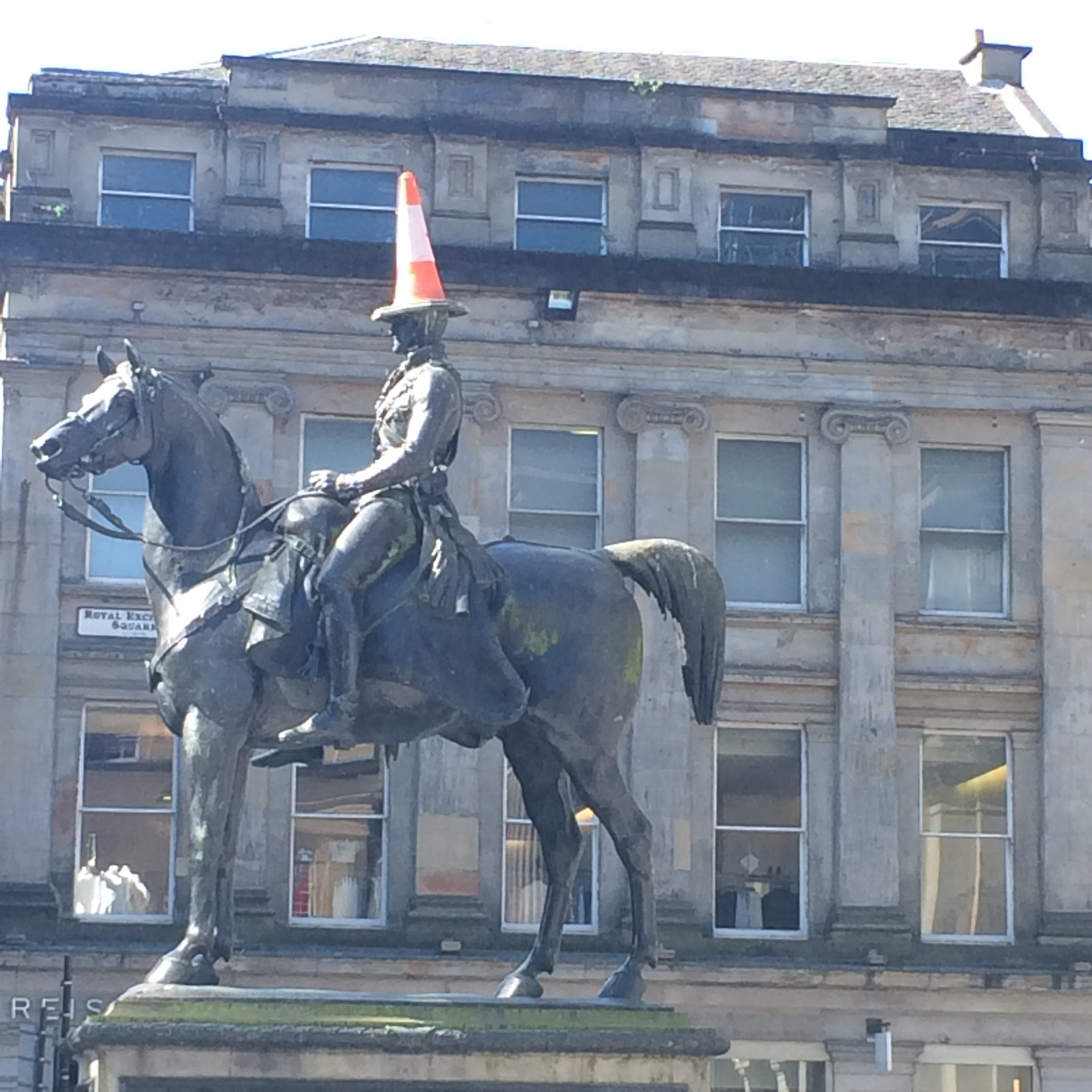 the Duke of Wellington statue stands tall with an iconic orange traffic cone on his head - once a prank, now a staple of Glasgow, pure Glaswegian humour